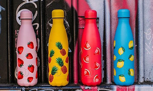 Four water bottles in a line each with a different fruit pattern.