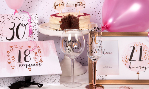 gifts for special birthdays arranged including a picture frame, wine glass, gift box, cake and balloon.
