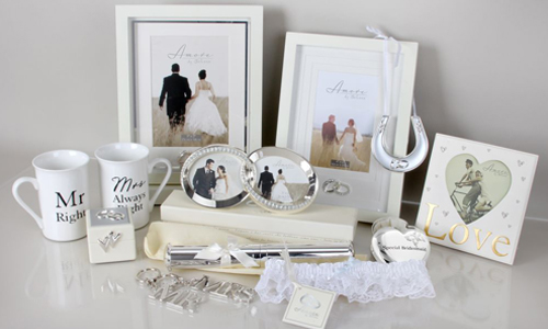 An arrangement of wedding gifts including mr and mrs mugs, photo frames and a silver horseshoe.